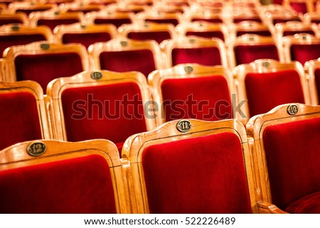 Sets on an empty theatre, taken with selective focus and shallow depth of field. Empty vintage red seats with numbers, teather chair, cinema seats. Movie theater auditorium with lines of red chairs.
