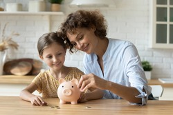 Setting good example. Young parent mother teach child little daughter girl to manage finances save money spend earnings with economy plan family budget. Friendly mom and kid thrift coins in piggybank
