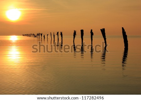 Setting sun above a line of fence posts, Great Salt Lake, Utah, USA.