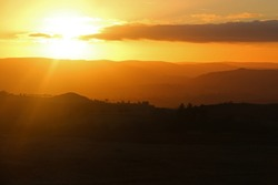 Setting sun in an orange sunset sky over the South Shropshire and Welsh Hills