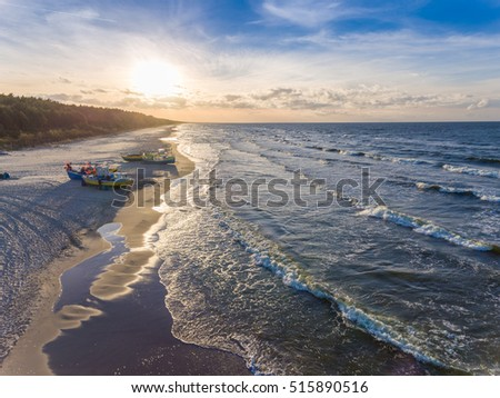 Setting sun over fishing boat moored at the beach in K??ty Rybackie, Poland Stock fotó ©