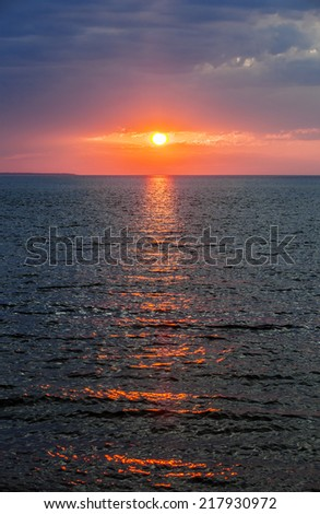 Setting sun with dramatic red sky over Atlantic Ocean in Prince Edward Island, Canada