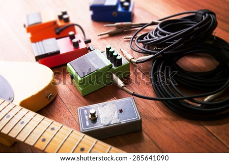 Setting up guitar audio processing effects. Electric guitar and stomp box type effectors and cables on studio floor. Intentionally shot with impressional feel, color and tone.