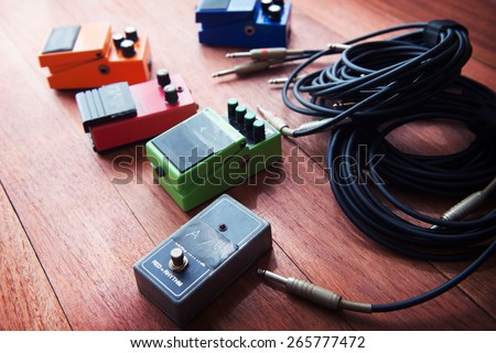 Setting up guitar audio processing effects. Electric guitar stomp box effectors and cables on studio floor. Focus is on forehand switch box. Intentionally shot with impressional feel and tone.