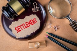 SETTLEMENT. Laws, litigation, lawyers and compromise concept. Wooden court hammer and magnifying glass on the table