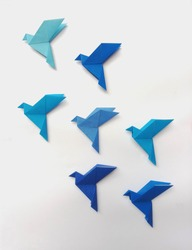 Seven blue Origami Birds are flying, leading by a light blue bird, isolated on white.