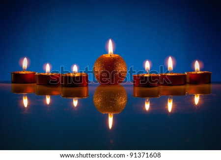 Seven burning candles over blue background