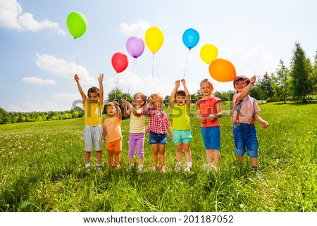 Seven children with balloons in green field