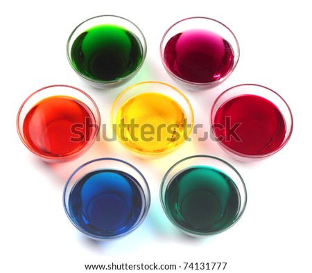 Seven glass caps with dyes for easter eggs isolated on white background