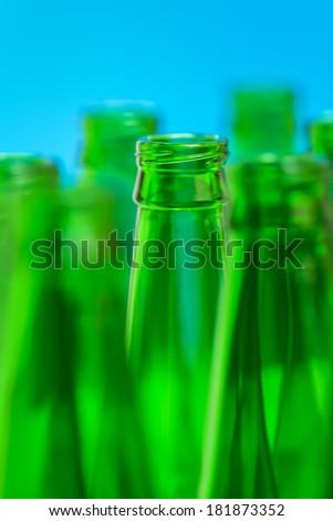 Seven green bottle necks on blue background, in center one bottle in focus.