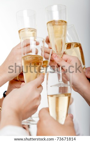 Seven hands raising champagne flutes on a toast