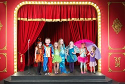 Seven happy children in costumes on red stage in theater, collage