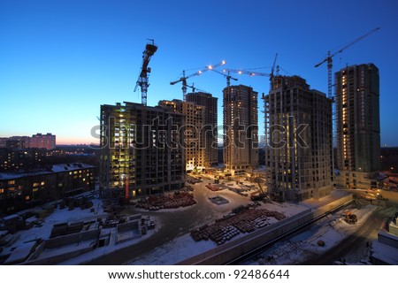 Seven high buildings under construction with cranes at evening stock photo