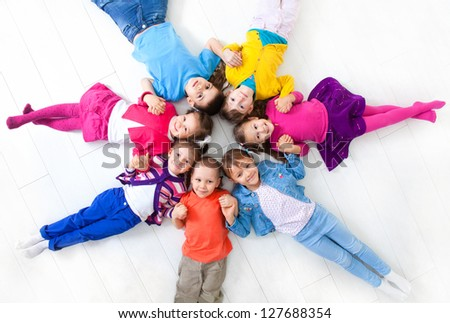 Seven kids are on the floor together. Top view