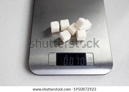 Seven lumps of refined sugar are weighed on a kitchen scale. Diet. Foto d'archivio ©