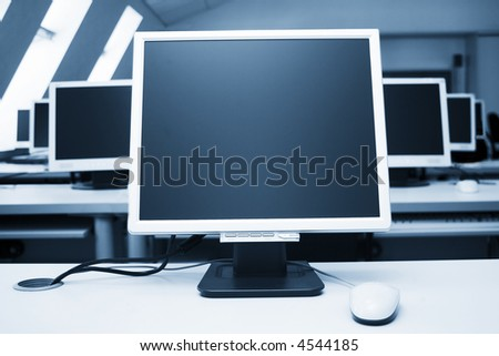 seven monitors in a computer class - stock photo