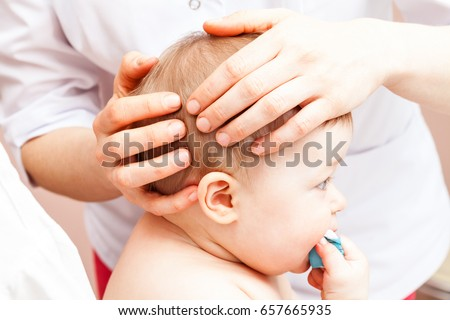 Seven month baby girl's head being manipulated by an osteopath - an alternative medicine treatment