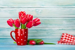 Seven red tulips bouquet in a red glass, The floor has two red tulips and one handkerchief placed in front of the blue wooden wall.