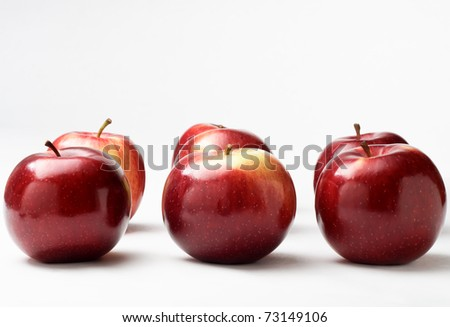 Seven shiny red apples in two rows of three with one at the back.