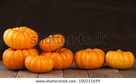 Seven Small Pumpkins Lined Up in a Row on Rustic Old Wooden Boards Against a Dark Brown Fabric Background with Copy Space