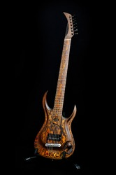 Seven-string electric guitar made of dark wood. Background for music and creativity.