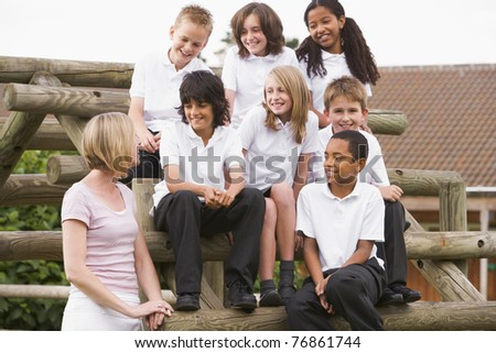 Seven students sitting on wooden structure with teacher standing beside them