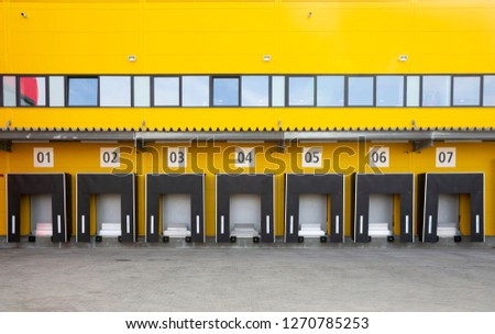 Seven truck loading docks at a distribution warehouse. Distribution hub for sorting packages and parcels. #1270785253