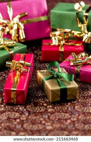 Seven wrapped gifts placed on a festive cloth. Background for any gift-giving occasion. Shallow depth of field.
