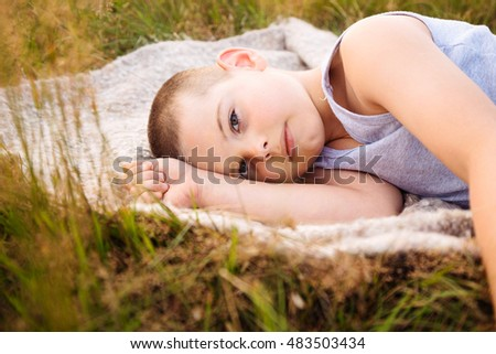 04d660b0ff8 Seven-year-old boy lying down in grass in summer. Relaxing rural lifestyle