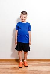 Seven-year-old European boy in sports uniform stands near white wall
