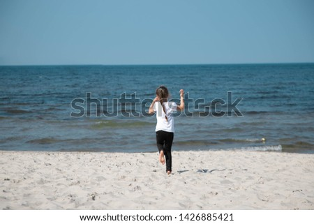 seven-year-old girl in a white T-shirt and black pants, pants with a long oblique running to the sea stretching her arms up. The little girl turned to the sea and ran #1426885421