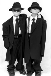 Seven year old twin boys dressing up as Blues Brothers in adult clothes.