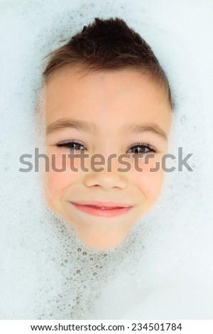 Seven years boy in a bubble bath filled with soap foam