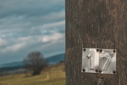 Seventeen (17) metal plate on a wooden electrical post in the middle of rural terrain with dark clouds and lonely tree in the background