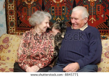 Seventy year old couple smiling in home on sofa