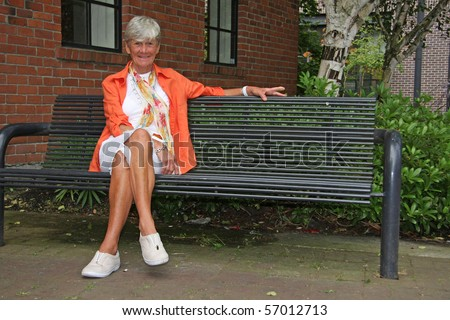 Seventy year old friendly lady seated on a park bench.