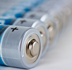 Several AA batteries in perspective closeup view on white background