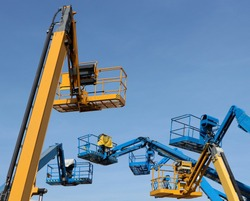 Several aerial working platforms of cherry picker against blue sky