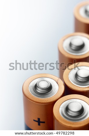 Several alkaline batteries on a light colored background,closeup