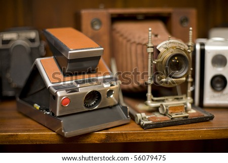 Several Antique Cameras on timber display shelf, including large format wooden camera. Deliberate shallow depth of field.