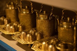 Several antique golden teapots made of brass are placed side by side.