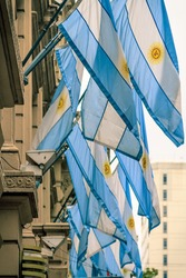 Several Argentine flags hung from a wall