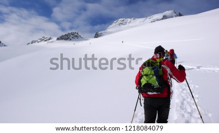 several backcountry skiers hike and climb to a remote mountain peak in Switzerland on a beautiful winter day
