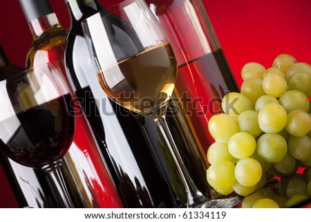 Several bottles of red and white wine glasses and grapes on a red background