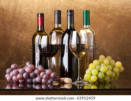 Several bottles of white and red wine, two glasses and grapes on a golden background