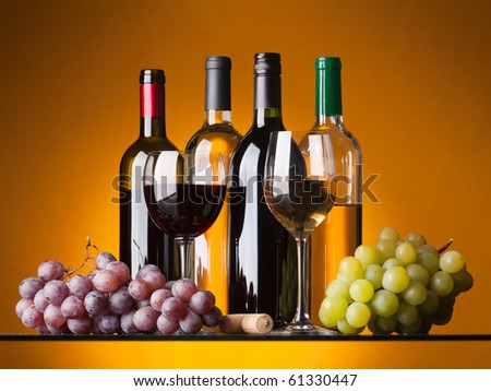 Several bottles of white and red wine, two glasses and grapes on an orange background - stock photo