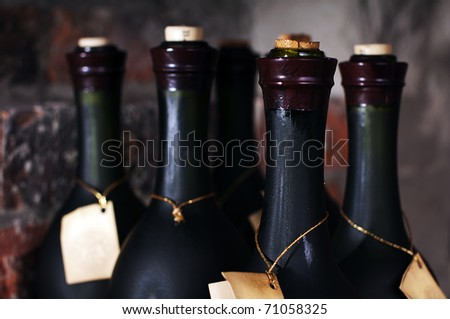 Several bottles of wine on brick background.In the old cellar. - stock photo