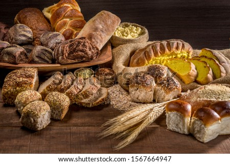 several breads made with sesame seeds, sunflower seeds,  corn meal, linsced, oatmeal, barley, rye, chia, pumpkin seed, poppy, nutmeg, on rustic wooden table