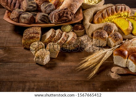 several breads made with sesame seeds, sunflower seeds,  corn meal, linsced, oatmeal, barley, rye, chia, pumpkin seed, poppy, nutmeg, on rustic wooden table, lettering