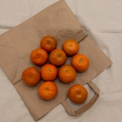 Several brightly colored tangerines are arranged on an eco-friendly paper bag. The background is beige fabric. Top view